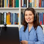 Friendly smiling woman with computer, webcam and headphone at a callcenter, hotline or helpdesk